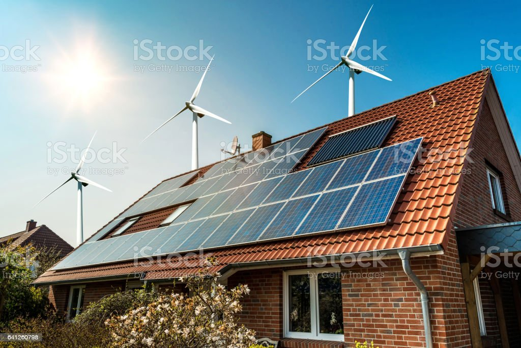 Solar panel on a roof and wind turbins arround stock photo