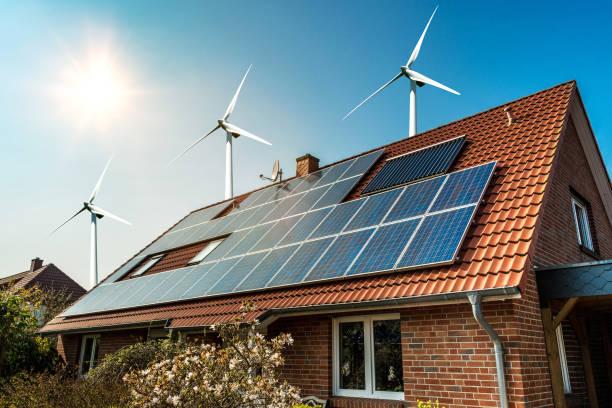 solar panel on a roof and wind turbins arround - pannelli solari foto e immagini stock