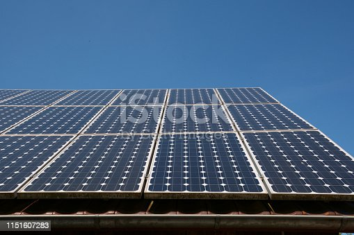modern solar cells or photovoltaic on the roof of an old woodshed with new gutter in front of azure sky