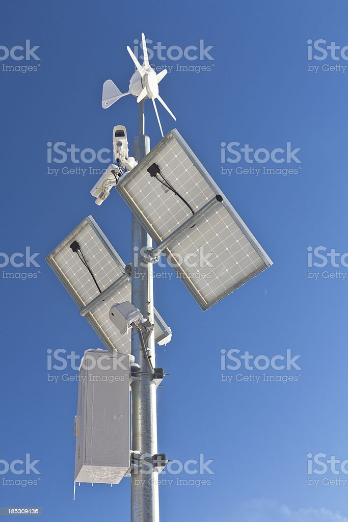 Solar panel, wind turbine and surveillance cameras stock photo