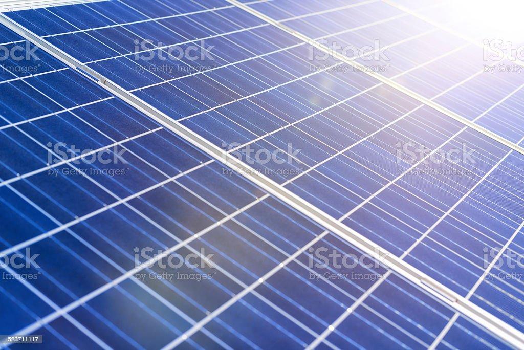 solar panels against a sunny sky with sun flares stock photo