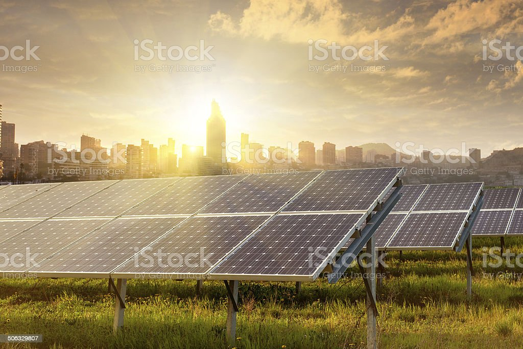 solar panels against city silhouette on sunset stock photo
