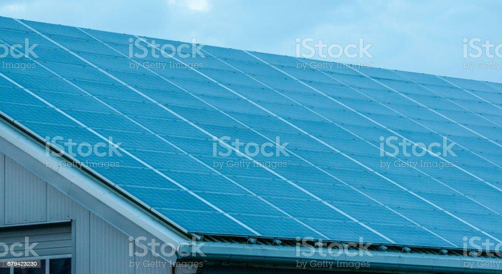 Panneaux solaires contre le bleu intense du ciel et les nuages photo libre de droits