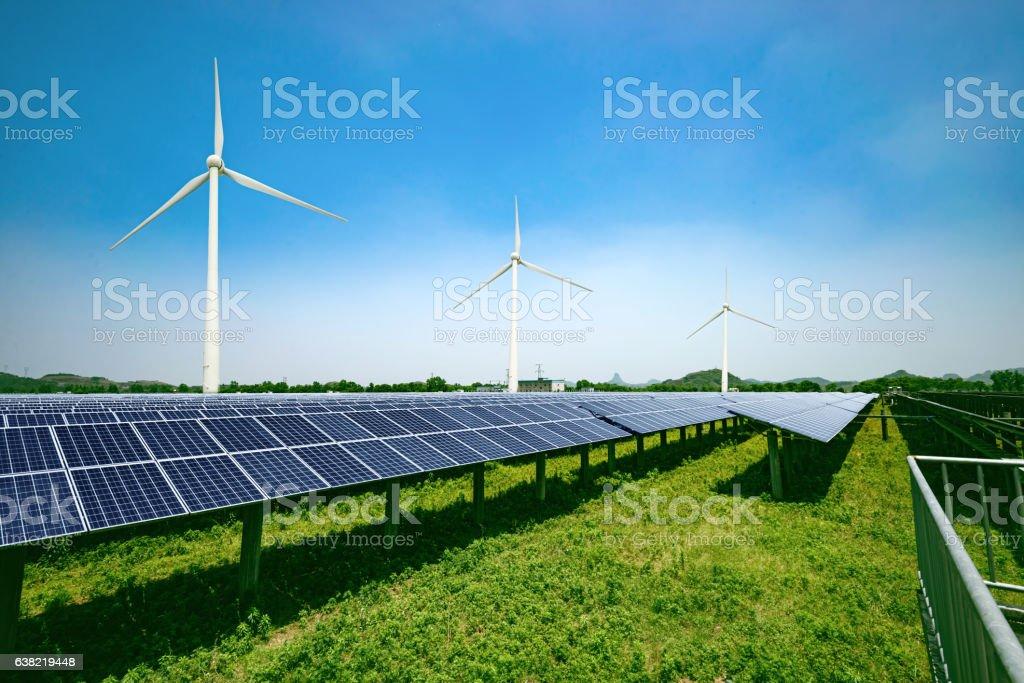 solar panels and wind generators under blue sky on sunset stock photo