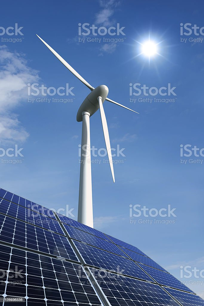Solar panels and wind turbine against a sunny sky stock photo