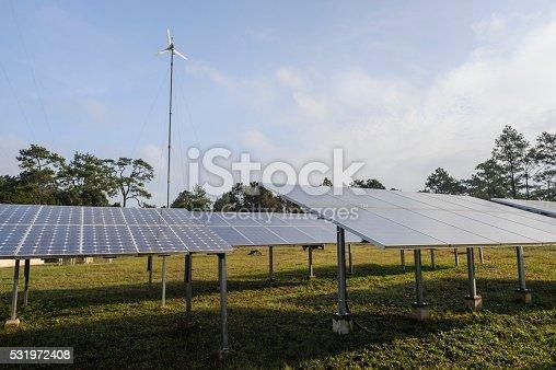 480763537 istock photo Solar panels and wind turbine on green grass. 531972408