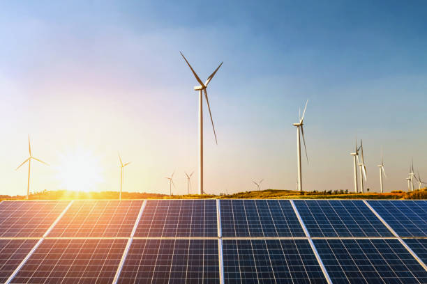 sonnenkollektoren und windkraftanlage bei sonnenuntergang auf dem hügel. konzept-idee-saubere energie - solarstrom stock-fotos und bilder