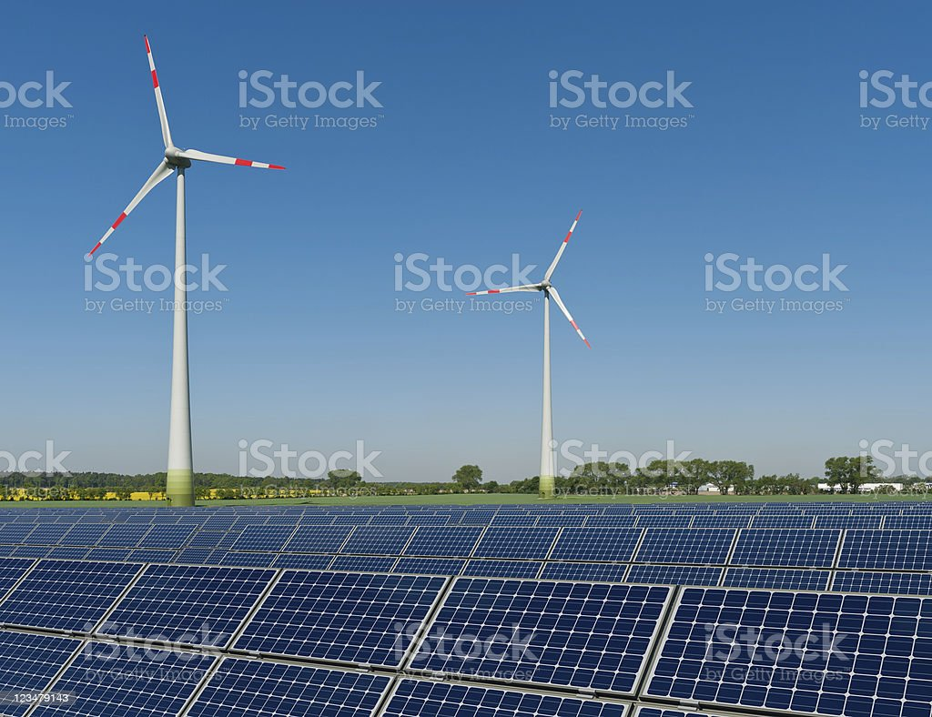 Solar panels and wind turbines against a rapeseed field stock photo