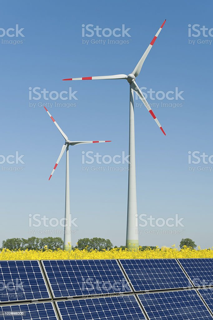 Solar panels and wind turbines in a rapeseed field stock photo