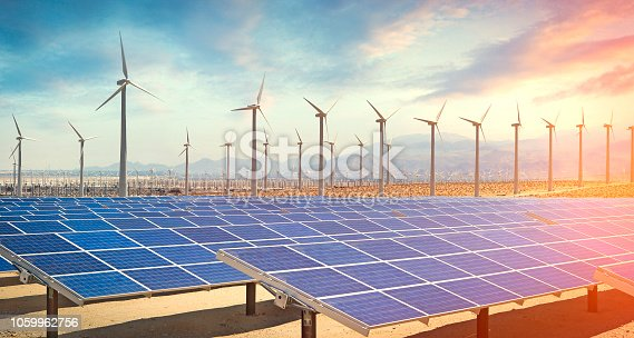 Solar panels and wind turbines in the desert producing renewable energy