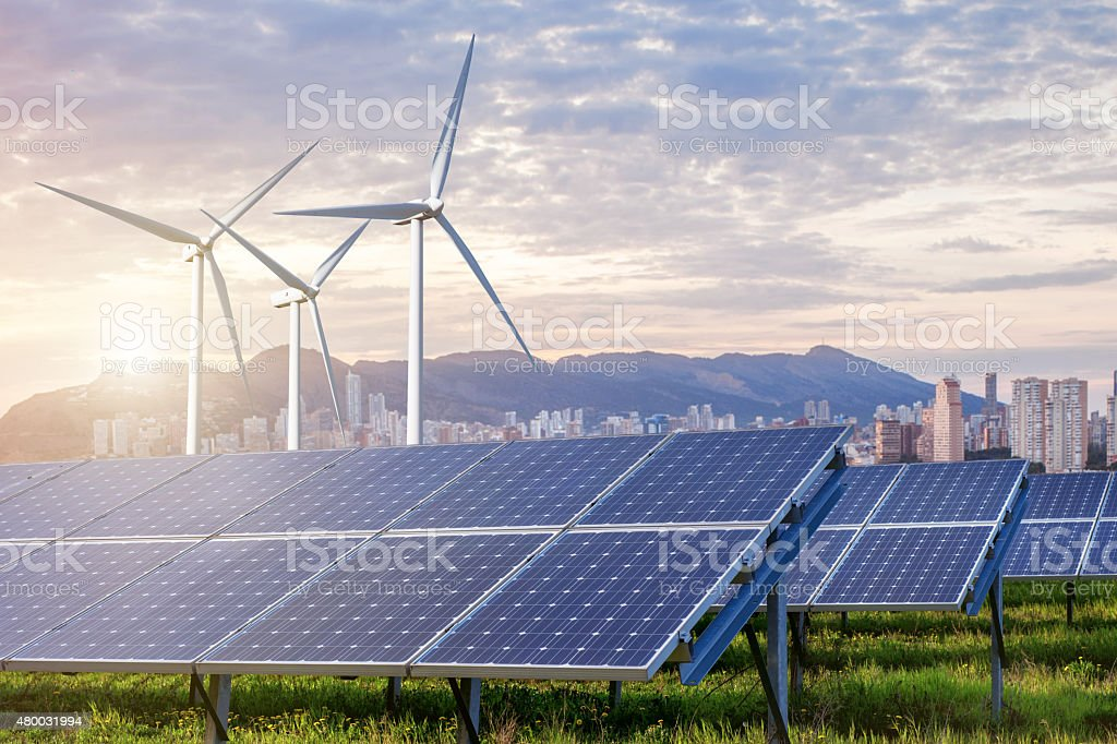 Solar panels and wind turbines with city stock photo