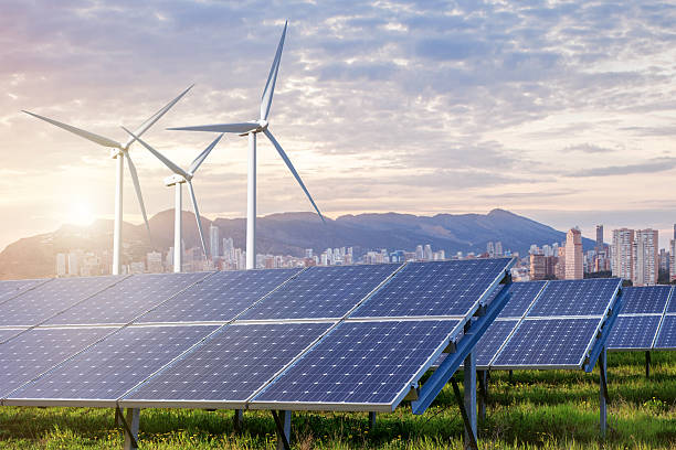 solar panels and wind turbines with city - power in nature stock photos and pictures