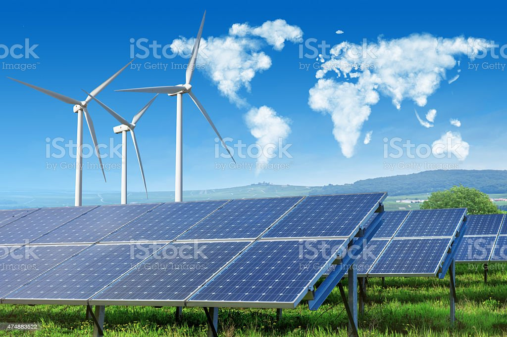 solar panels and wind turbines with world map in sky stock photo