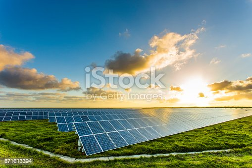 Solar panels at sunrise with cloudy sky in Normandy, France. Solar energy, modern electric power production technology, renewable energy concept. Environmentally friendly electricity production.
