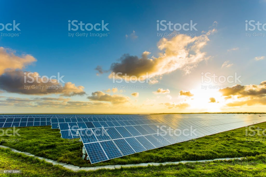 Solar panels at sunrise with cloudy sky in Normandy, France. Solar energy, modern electric power production technology, renewable energy concept. Environmentally friendly electricity production stock photo