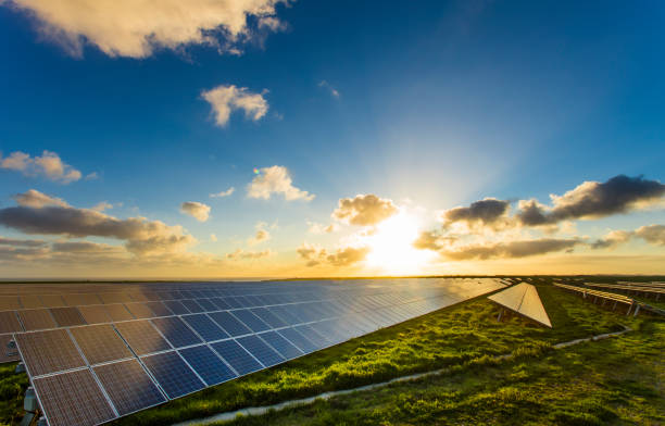 solar panels at sunrise with dramatic cloudy sky in normandy, france. modern electric power production technology. environmentally friendly electricity production - responsible business stock photos and pictures