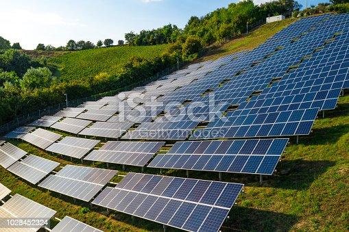 1170098138istockphoto Solar panels fields on the green hills 1028452324