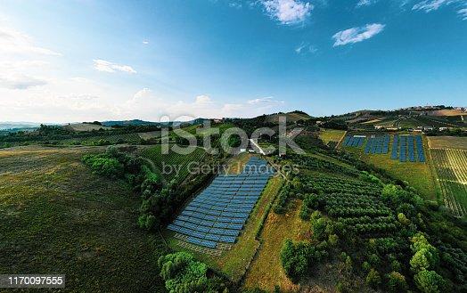 1170098138istockphoto Solar panels fields on the green hills 1170097555