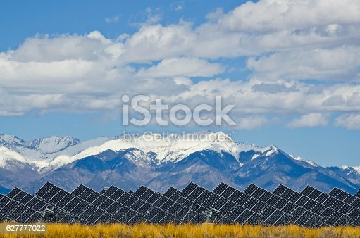 A series of large solar panels forms a symmetrical line at a power plant in the San Luis Valley of central Colorado.  The installation must be one of the most scenic in the United States, as it backs up to the snow capped Sangre de Cristo Mountains.  These panels utilize a tracking system to follow the sun, collecting its energy and using photovoltaic cells to transform the sunlight into electricity.