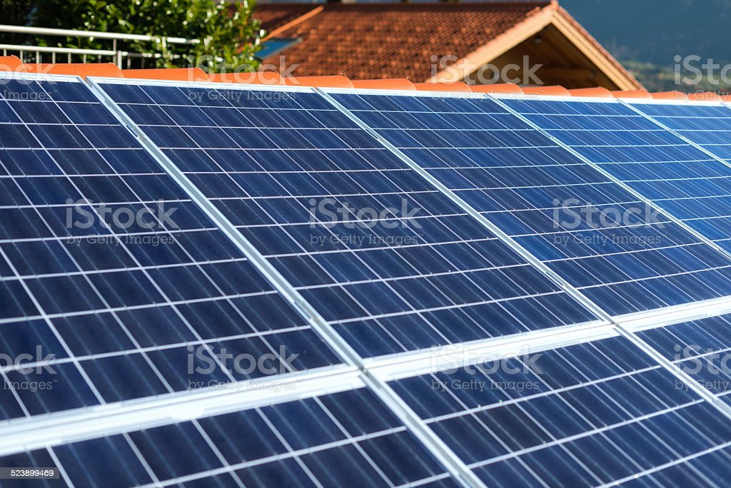 solar panels mounted on house rooftop stock photo