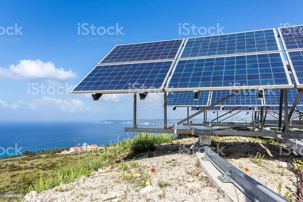 Solar panels near blue sea and monastery stock photo