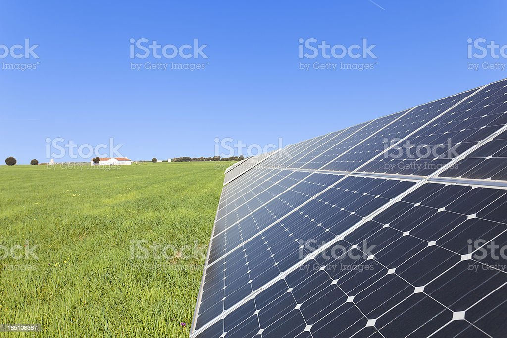 Solar panels on a green field and blue sky royalty-free stock photo