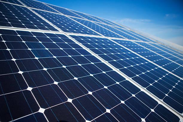 solar panels on a sunny day against clear blue sky - 太陽能電池板 個照片及圖片檔