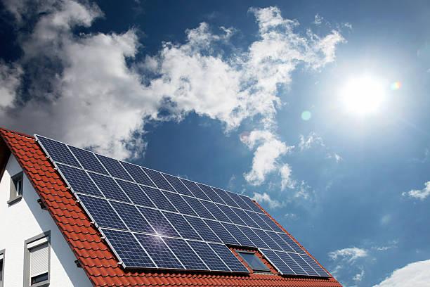 solar panels on house roof - zonnepanelen stockfoto's en -beelden