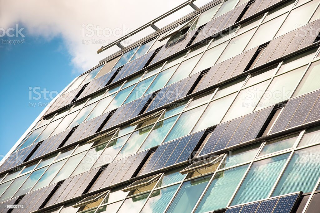 solar panels on modern glass facade with cloud reflections stock photo