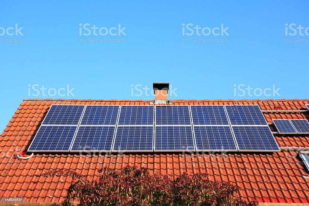 solar panels on red roof  and chimney stock photo