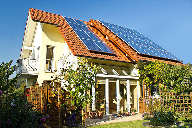 solar panels on roof of house in late summer - bontbladig stockfoto's en -beelden