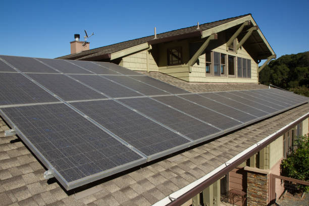 solar panels on roof of house solar panels on roof of house. horizontal orientation, blue sky, gray panels on brown roof. solar panels photos stock pictures, royalty-free photos & images