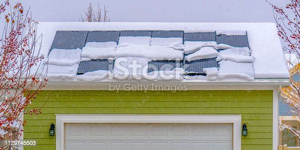 Solar panels on snow covered roof in winter. Solar panels on snow covered roof of a home's garage in Daybreak, Utah. Sheets of snow slides down the slippery surface of the solar panels.