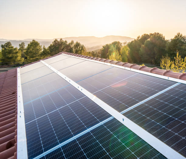 Solar panels on the roof of a House at sunset stock photo