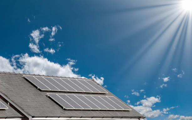 Solar Panels On The Roof Of A House Under A Bright Sunny Sky stock photo