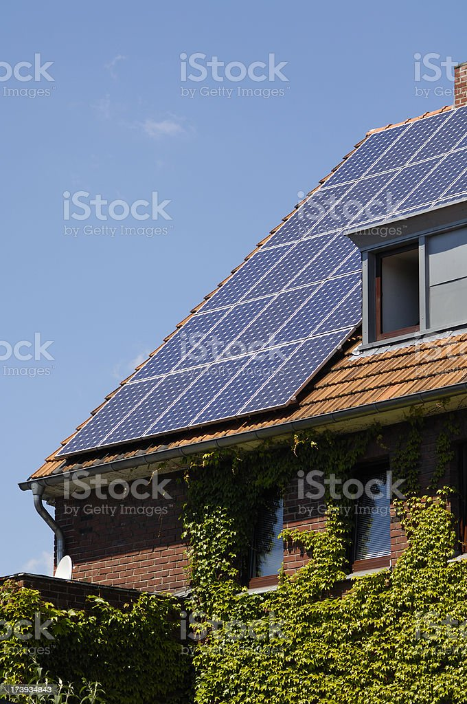 Solar panels on the roof of an ivy covered house royalty-free stock photo