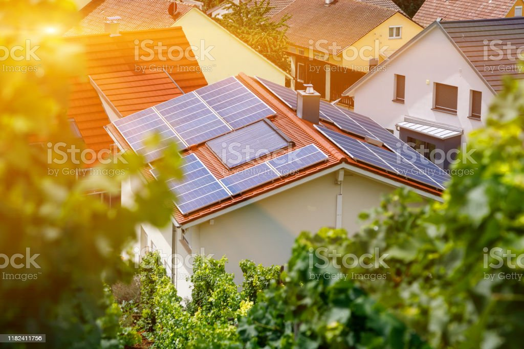 Solar panels on the tiled roof of the building in the sun. Top view through grape leaves. Selective focus. - Royalty-free Blue Stock Photo