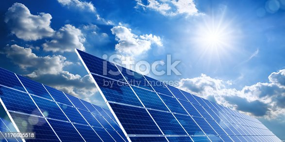 Two large solar panels under the blue sky with the sun and clouds