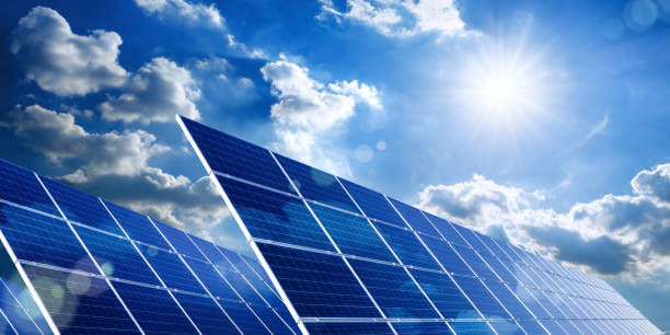 Solar panels with blue sky, sun and clouds stock photo