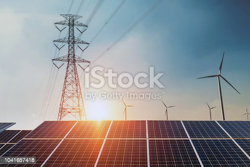 Solar panels with electricity pylon and wind turbine Clean power energy concept. sunset background