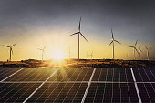 solar panels with wind turbine and sunset .concept power energy in nature