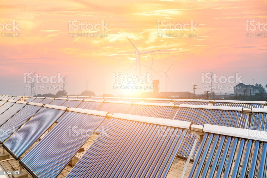 Solar panels with wind turbines and electricity pylon at sunset. Clean energy concept. stock photo