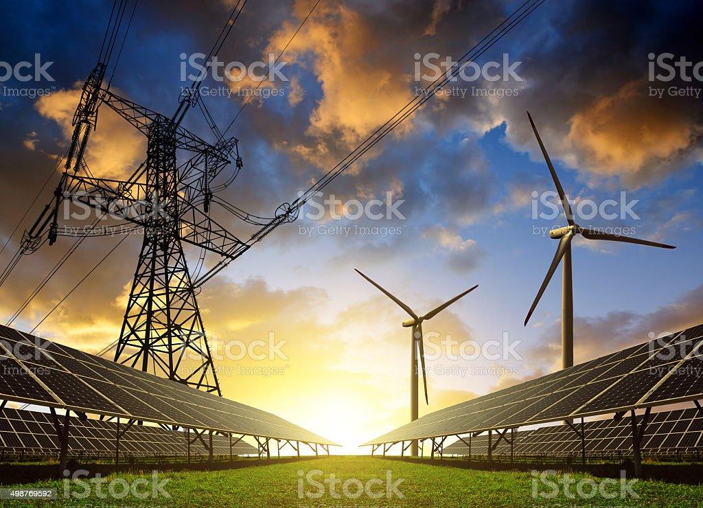 Los paneles solares con turbinas eólicas y la torre de conducción eléctrica en sunset. - foto de stock