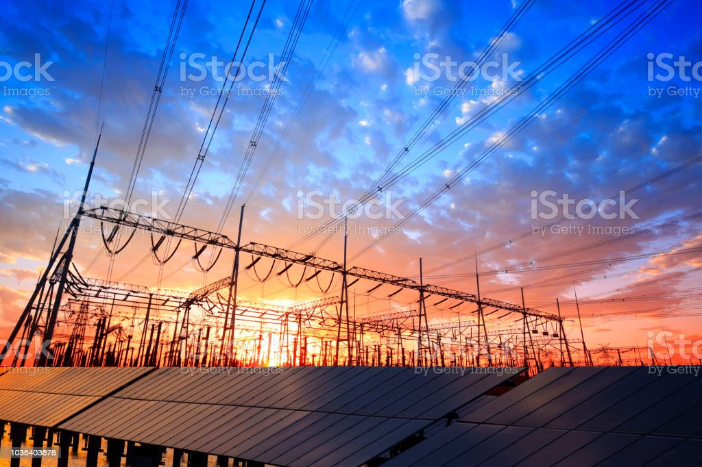 Solar photovoltaic panels and substations in the evening stock photo
