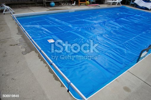 A solar cover extended out onto the top of a swimming pool.