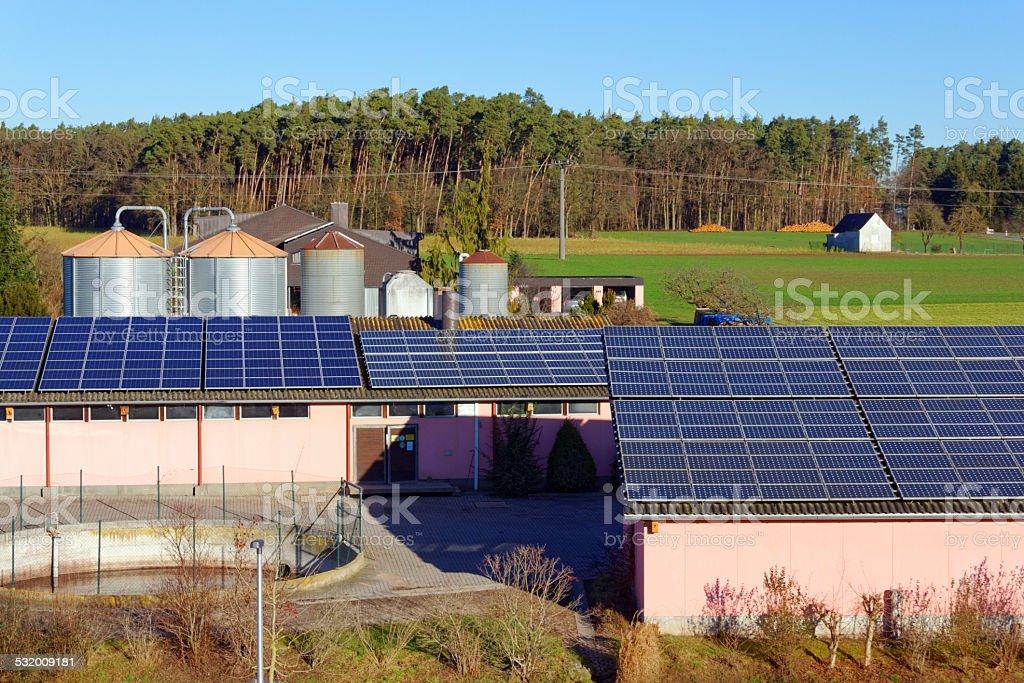 solar power panels with storage silo stock photo