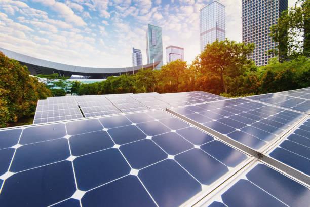 planta de energía solar en la ciudad moderna, sostenible de energía renovable - cuestiones ambientales fotografías e imágenes de stock
