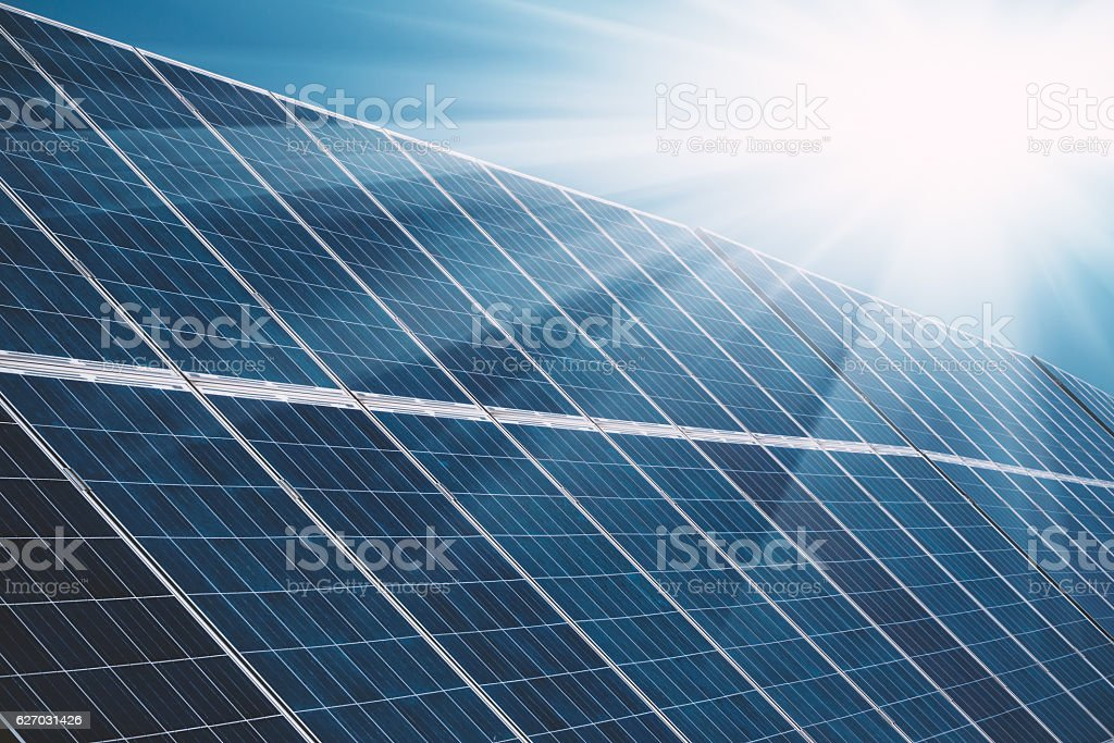 Solar power plant panels with sun rays and blue sky stock photo
