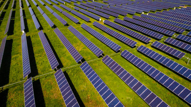 Solar power plant producing clean energy above rows and rows of solar panels stock photo