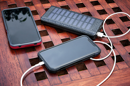 Solar power station charging smartphones under sunlight with clouds reflecting on screens